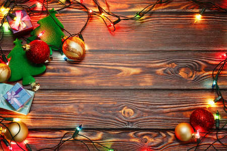 Symbols of winter holidays - Christmas decorations and New Year tree toys, gift boxes and colorful garland - prepared for home decoration on wooden background. Top view, place for text.