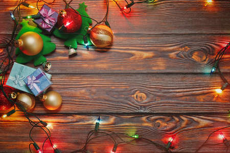 Christmas tree toys, gifts in tiny boxes, shiny garland and New Year ornaments prepared for winter holidays celebration on wooden background. Top view capture, place for text. Standard-Bild