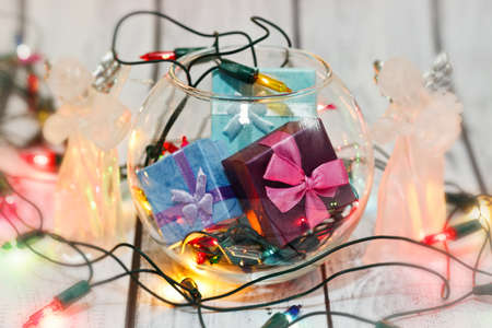 Traditional winter holidays - New Year and Christmas decorations - gifts boxes, angel figurines and Christmas tree colorful garland. Celebrate preparations concept. Selective soft focus.