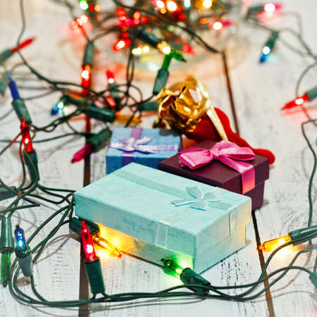 Tiny gift boxes surrounded by colorful shiny garland. Christmas and New Year presents and celebration preparations concept. Square capture, selective focus and star filter effect. Standard-Bild