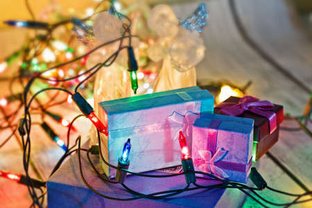 Heap of tiny gift boxes - New Year or Christmas presents concept with angels figurines and colorful garland. Traditional celebration preparations. Selective soft focus, close-up capture.