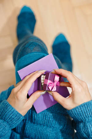 Female person in warm dress and knee height socks unpacking the gift box with pearl jewelry. Saint Valentine or Christmas presents concept. Overhead top view capture, selective focus.