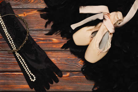 Elements of black swan image - classic russian ballet outfit - pointe hard shoes, black feather boa, high gloves, diadem and pearl necklace. After dancing show concept. Top view.