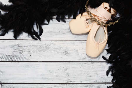 Classic matt ballet shoes with metal soles with satin ribbons and some dancing show props - feather boa and diadem on white wooden theater stage. Ballet show concept. Top view, place for text.