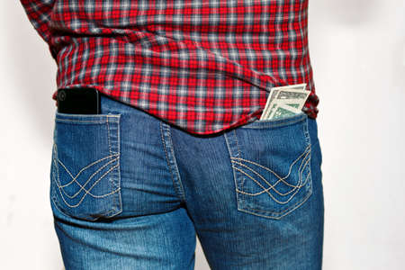 Male person in work outfit - checkered shirt and classic jeans. Cell phone and stack of US dollars currency unsafe stored in back pockets. Pickpocket danger concept. Capture from back, no face. Standard-Bild