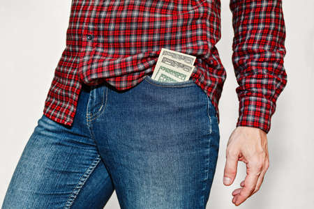 Young male person in classic checkered shirt and blue jeans pants with a stack of US dollars currency in front pocket. Unsafe money storage, pickpocket danger concept. No face capture.