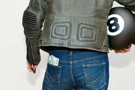 Male person wearing vintage style leather jacket with an old school motorcycle protective helmet in hand and with stack of US dollars in back pocket. Biker outfit concept. Capture from back, no face.