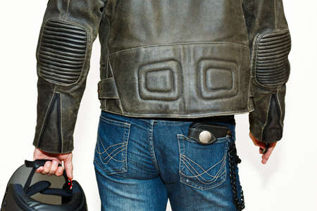 Male person in vintage shabby protective leather jacket and worn blue jeans with leather wallet in back pocket and with motorcycle helmet. Biker outfit concept. Capture from back, no face.