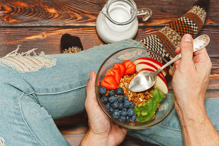 Young male person in torn jeans and cozy warm socks sitting on rough wooden rural style floor and having healthy breakfast of granola, fruits and berries and milk. First person or overhead top view.