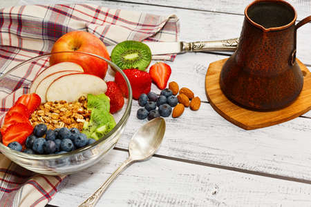 Delicious ready to eat breakfast including wholegrain granola flakes with apples, kiwi, strawberry and blueberry and a traditional eastern copper coffee pot. Meal served on rural style table.