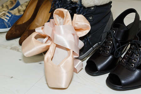 Pair of silky classic ballet dancing shoes in front of female person shoes collection including winter boots, summer ankle boots, sneakers and other. Close-up capture, selective focus.