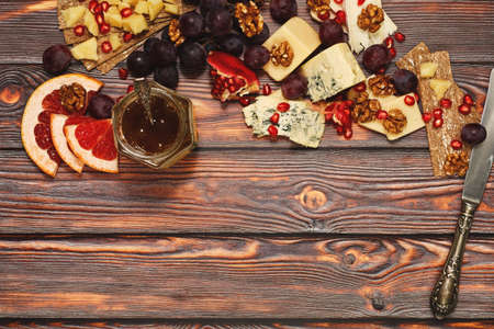 Plenty varieties of refined cheese - camembert, roquefort, parmeasn and gouda with fresh juicy fruits, walnuts and rye crackers. Healthy and delicious snack, wine appetizer. Top view, place for text. Foto de archivo