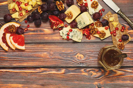 Refined appetizer, perfect as wine snack. Few variations of gourmet aged cheese with different fruits and, rye crackers, nuts and gooseberry jam. Served on rural style wooden table, top view.