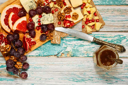 Light snack in european cuisine tradition on cutting board, including different cheeses, fruits, walnuts, crackers and jam, served on rural vintage style wooden table. Top view with place for text.