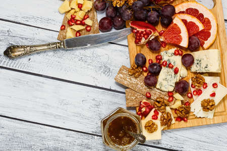 European cuisine classic cheese board - four varieties of gourmet ripped cheese on vintage loft style wooden table, served with fresh fruits, nuts, crackers and jam. Top view, place for text.