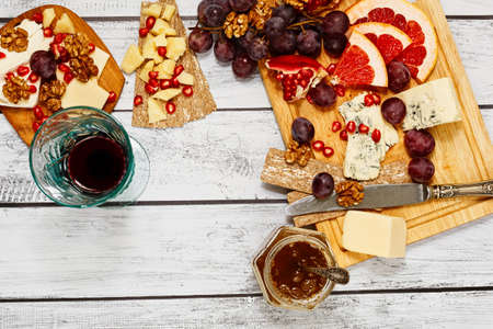 Refined cheese snack - plenty varieties of gourmet european cheese with fresh fruits. rye crackers and walnuts on a cutting board and a glass of red wine on wooden rural style table. Top view.
