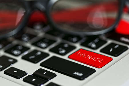 Updating software applications or computer hardware concept - laptop keyboard with red UPGRADE button instead of enter key and nifty sunglasses on it. Close-up capture, selective focus.