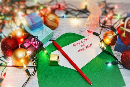 Writing holiday postcards concept - Christmas and New 2018 Year congratulations for friends and relatives. Christmas decorations like garland and toys nearby. Close-up capture, selective focus.