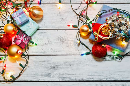Winter holidays preparations in full swing - vintage style New Year tree toys and traditional Christmas decorations, gift boxes and shiny garland on rural style wooden background. Top view.