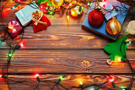 Wooden surface in rural style with traditional winter holiday symbols on it - tiny gift boxes, New Year tree toys and Christmas decorations and shiny colorful garland. Top view with place for text.