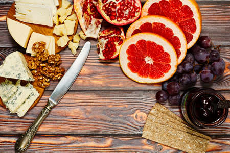 Ingredients for refined snack or appetizer collected on wooden table in rural style - plenty varieties of gourmet european cheese, fresh fruits, walnuts, rye crackers and cherry jam. Top view capture.