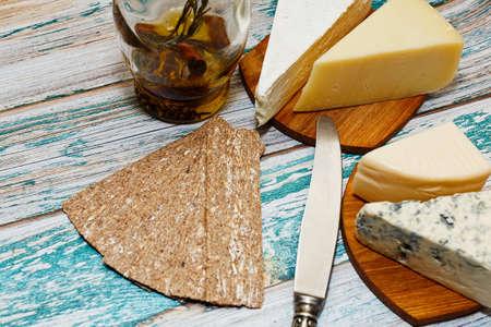 Cooking moment - variety of refined european cheese, olive oil and rye crackers on rural style rough painted table. Red wine snack or light healthy diet appetizer ingredients. Close-up capture.