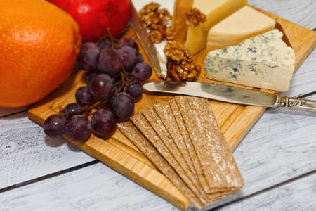 European cuisine style appetizer - gourmet cheese with fruits, rye crackers and walnuts. Perfect light lunch or red wine snack, healthy, nourishing dieting concept. Selective focus, close-up capture. Standard-Bild