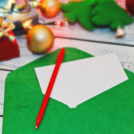 Last preparations for winter holidays concept - blank postcard ready to sign with Christmas and New Year congratulations and some traditional decorations. Selective soft focus, close-up capture.