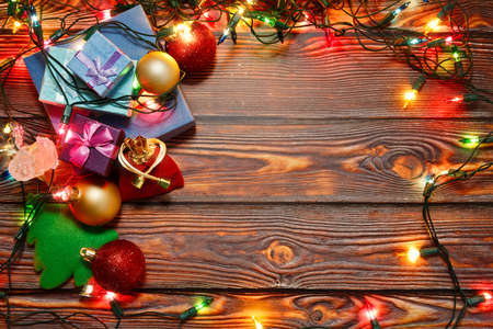 New Year and Christmas celebration in full swing - gifts are ready to present and collected in a pile decorated by toys and shiny garland on wooden background. Top view capture, place for text.