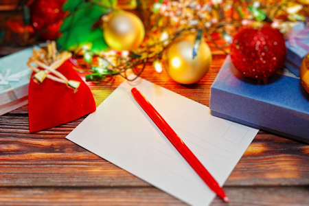 Winter holidays celebrations preparing and signing cards with congratulations for friends and relatives. Postcard and variety of Christmas and New Year decorations. Selective focus, close-up capture.