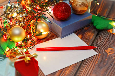 Writing winter traditional holidays greetings and congratulations postcards - blank card, New Year tree toys and Christmas decorations on wooden background. Close-up capture, selective focus.