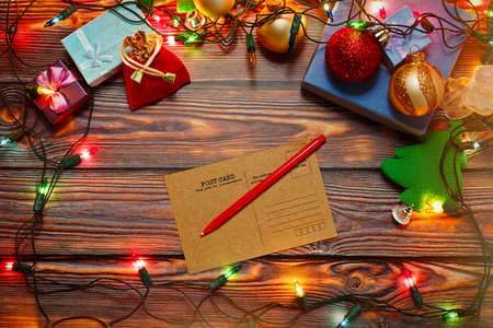 Writing New Year and Christmas congratulations postcards for friends and relatives - blank vintage card on wooden table surrounded by decorations, tree toys and garland. Top view, place for text.