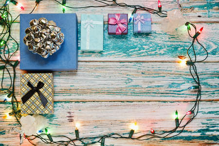 Some New year or Christmas gifts packing in tiny boxes and collected on wooden rural style rough painted surface with a frame of colorful shiny garland. Winter holidays idea. Top view, place for text.