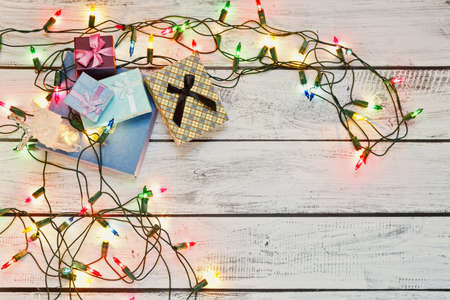 Christmas and New Year celebration metaphor - pile of gift boxes framed by colorful garland lie on wooden background and waiting for traditional winter holidays. Flat lay with place for text.