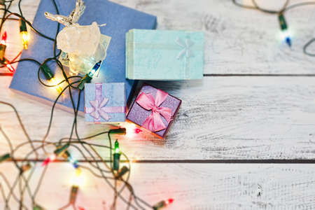New Year gift boxes collected in a heap on wooden surface with angel figurine, symbol of Christmas, and surrounded by colorful shiny garland. Selective focus, top view with place for text.