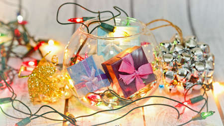 Winter holidays still life - gift boxes in glass vase, New Year decorations, shiny garland and traditional Christmas symbols - angels. Celebration concept. Wide screen capture. Selective focus. Standard-Bild