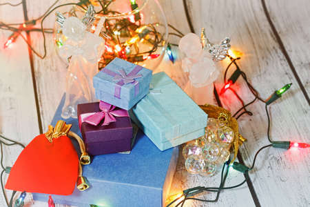 Ready to present and celebration Christmas and New Year gift boxes with an angel figurines nearby and traditional colored shiny garland on wooden background. Winter holidays concept. Close-up capture.