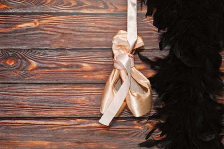 Pair of silky ballet shoes suspended on ribbon and black feather boa nearby on wooden background. Ballet traditional theater and dancing show concept, behind the stage metaphor. Place for text.