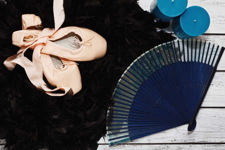 Some props and scenic costume elements on wooden stage - traditional ballet shoes, hand fan, candles and black feather boa - probably Black Swan role outfit. Classic ballet show concept.  Top view.