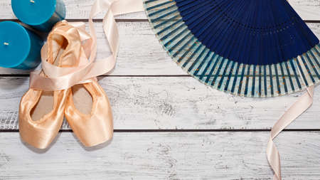 Traditional ballet shoes calling pointe with hard metal insole and some dancing show props lie on wooden theater stage after the ballet show. Behind the stage concept. Wide screen capture, top view. Standard-Bild