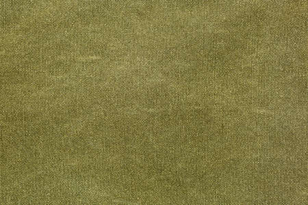 Horizontal piece of rough canvas fabric, olive colored. Vintage style unevenly painted dense textile with traces of usage.