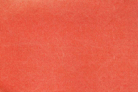 Horizontal background capture of faded red canvas fabric texture. Rough dense rag of retro style textile with traces of usage.