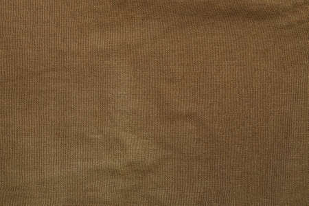 Close-up horizontal background capture of piece of rough canvas cloth, khaki colored. Textile is crumpled and have traces of worn and usage.