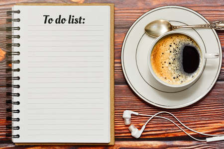 Blank notepad with a to do list and a cup of black espresso coffee on the wooden table. Planning the day and filing up checklist while having a coffee break concept. Contemporary lifestyle concept.