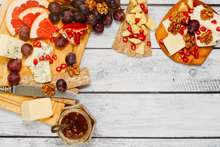 Plenty varieties of refined european cheese with different fruits, nuts, crackers and fresh jam on the wooden rural style table. Ready to eat snack. Healthy lifestyle concept. Top view. Stock Photo