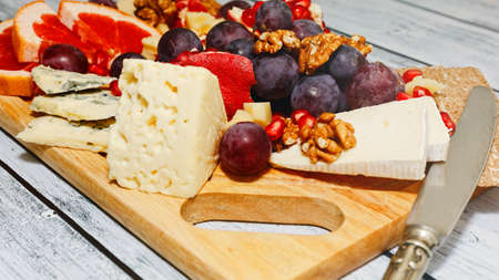 Few kinds of gourmet cheese with fresh fruits, crackers and walnuts - perfect wine snack or light appetizer in european style. Healthy dieting concept. Served on rural style table. Close-up capture.