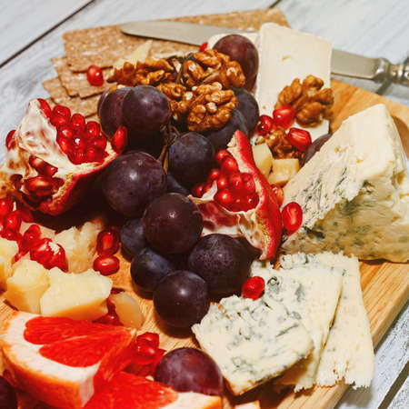 Few varieties of refined cheese chopped and sliced and mixed with walnuts, grapes,garnet and grapefruit served on board with rye crackers. European style snack concept. Close-up square capture. Standard-Bild