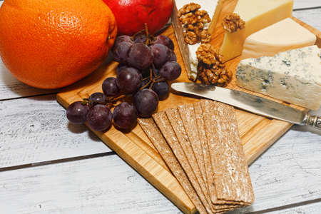 Classic european cuisine snack - plenty varieties of gourmet cheese with rye crackers, fresh fruits and walnuts served on raw cutting board on the rough wooden table in loft style. Close-up capture. Standard-Bild