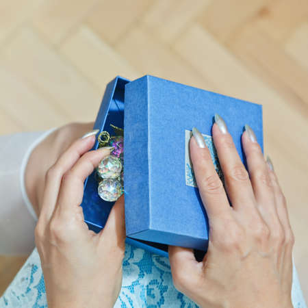 Teenage female person with manicure in blue dress opens a box with gift - jewelry or decoration - holding it on the knees. Holiday presents concept. First person top view, square capture. Standard-Bild