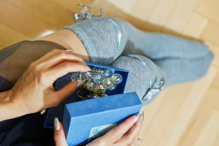 Young adult woman in knee heights socks opening a box with a gift holding it on her knees. Holiday present concept, suitable for Saint Valentine day or Birthday. First person top view.